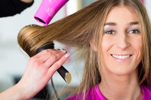 Kobieta u fryzjera ma wysuszonego włosy