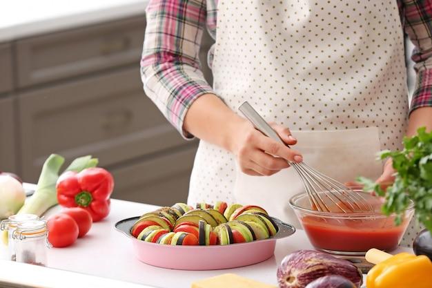 Kobieta ubieranie świeżych warzyw z sosem pomidorowym w kuchni