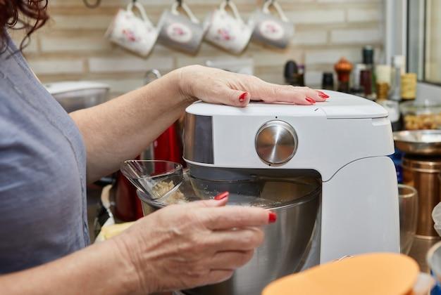 Kobieta ubija ciasto mikserem, aby przygotować muffinki z suszonymi pomidorami