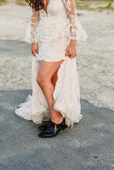 Kobieta ubrana jak panna młoda z męskich butów