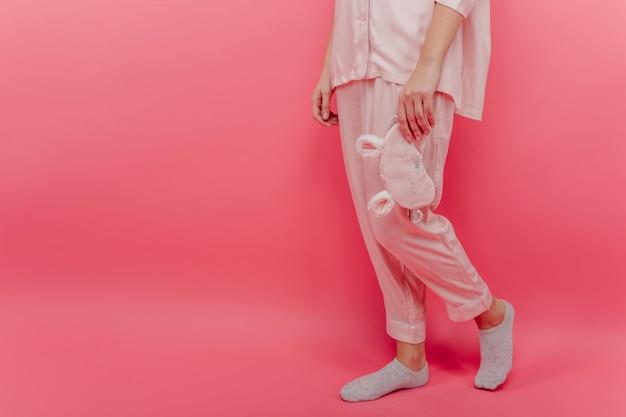 Kobieta ubrana jest w przytulny bawełniany kombinezon nocny stojący na różowej ścianie. portret modelki w piżamie i szarych skarpetkach.