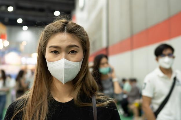 Kobieta ubrana maska ochronna stojąca na wystawie i być zatłoczona infekcją wirusową