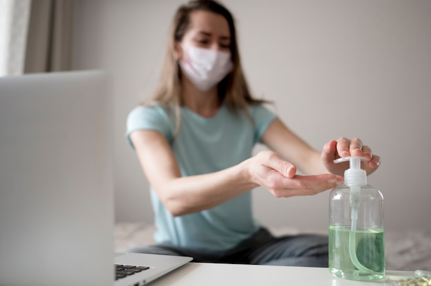 Kobieta ubrana maska wewnątrz i za pomocą dezynfekcji rąk