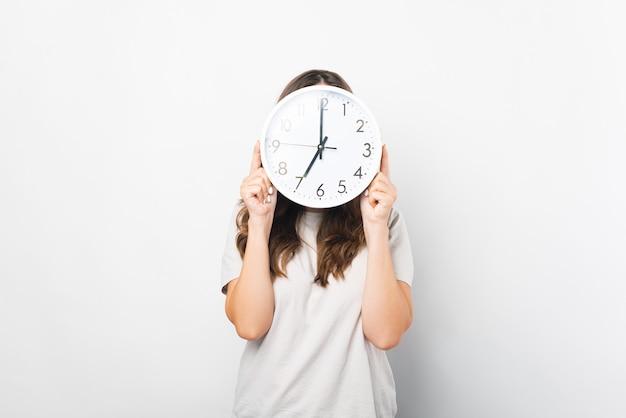 Kobieta ubrana na biało trzyma i zakrywa twarz okrągłym zegarem.