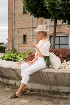 Kobieta ubrana na biało za pomocą swojego telefonu długi widok