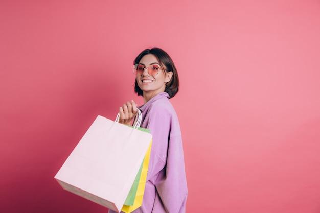 Kobieta ubrana na co dzień sweter na tle szczęśliwy korzystających z zakupów trzymając kolorowe torby na sobie letnie okulary przeciwsłoneczne