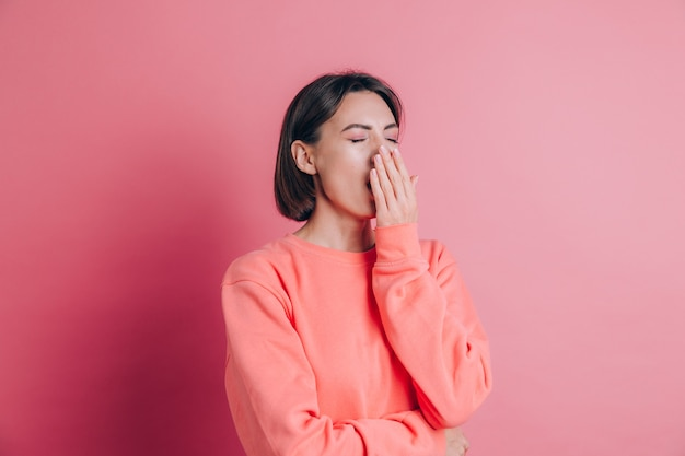 Kobieta ubrana na co dzień sweter na tle znudzony ziewanie zmęczony zakrywanie ust ręką. niepokój i senność