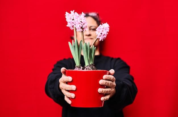 Kobieta ubrana na czarno trzyma czerwoną doniczkę z różowymi hiacyntami na czerwonej ścianie
