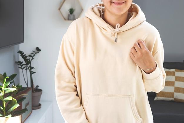 Kobieta ubrana w beżową bluzę z kapturem makiety makieta dzień matki w jasnym wnętrzu domu