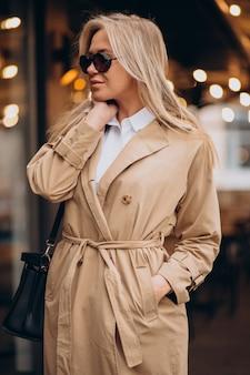 Kobieta ubrana w beżowy płaszcz i spacerująca po ulicy w boże narodzenie