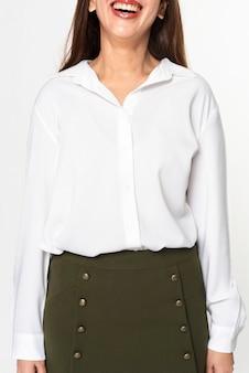 Kobieta ubrana w białą koszulę z długim rękawem i zieloną spódnicę