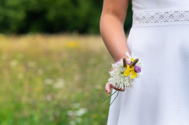 Kobieta ubrana w białą sukienkę i trzymająca piękne kolorowe kwiaty