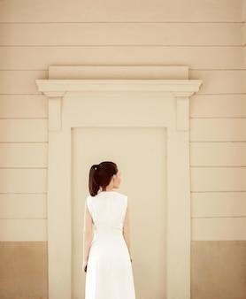 Kobieta ubrana w białą sukienkę przy beżowej ścianie