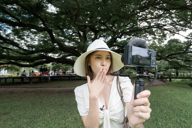 Kobieta ubrana w białą sukienkę robi selfie pod drzewami giant monkey pod w kanchanaburi w tajlandii.