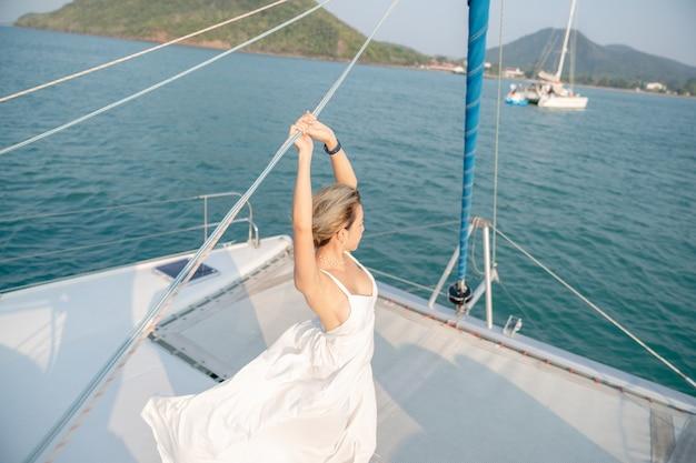 Kobieta ubrana w białą sukienkę zrelaksować się na jachcie żaglowym, romantyczny zachód słońca.