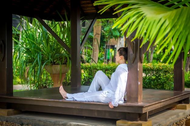 Kobieta ubrana w białe szaty siedzi w altanie po ćwiczeniu jogi