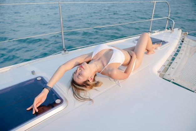 Kobieta ubrana w biały strój kąpielowy zrelaksować się na jachcie żaglowym, romantyczny zachód słońca.