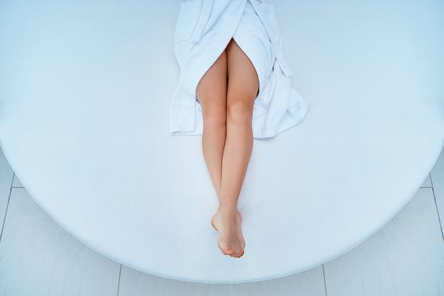 Kobieta ubrana w biały szlafrok z pięknymi, gładkimi, szczupłymi długimi nogami