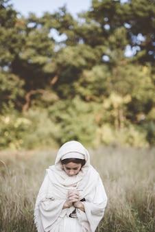 Kobieta ubrana w biblijną szatę i modląca się, patrząc w dół