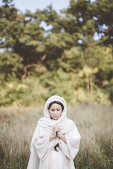 Kobieta ubrana w biblijną szatę i modląca się z zamkniętymi oczami