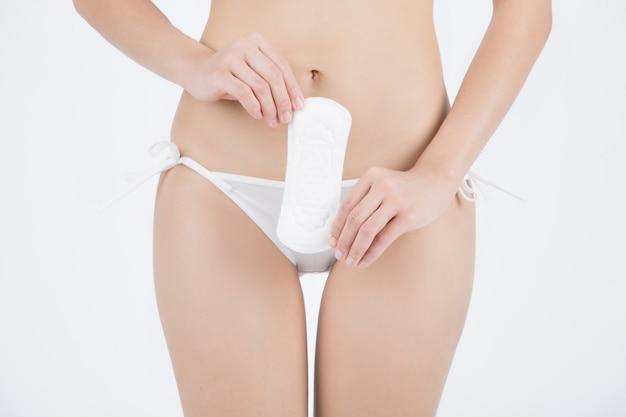 Kobieta ubrana w bikini gospodarstwa podpaski higienicznej