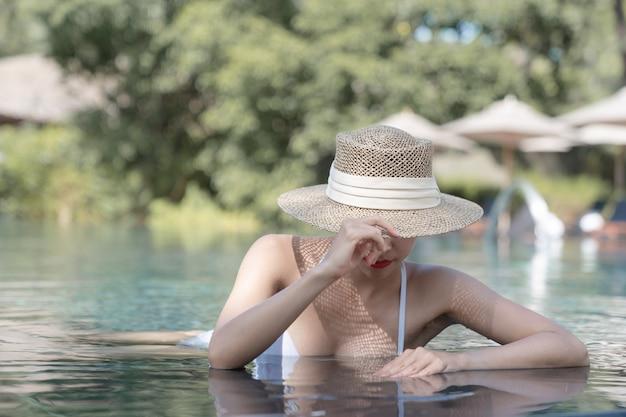 Kobieta ubrana w bikini i słomkowy kapelusz obejmujące twarz relaks w basenie. koncepcja zabiegów spa.