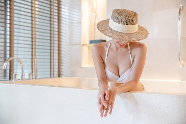 Kobieta ubrana w bikini i słomkowy kapelusz obejmujące twarz relaks w wannie z hydromasażem. kuracja spa