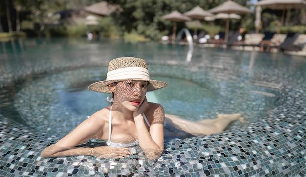 Kobieta ubrana w bikini i słomkowy kapelusz relaks w basenie. koncepcja zabiegów spa.