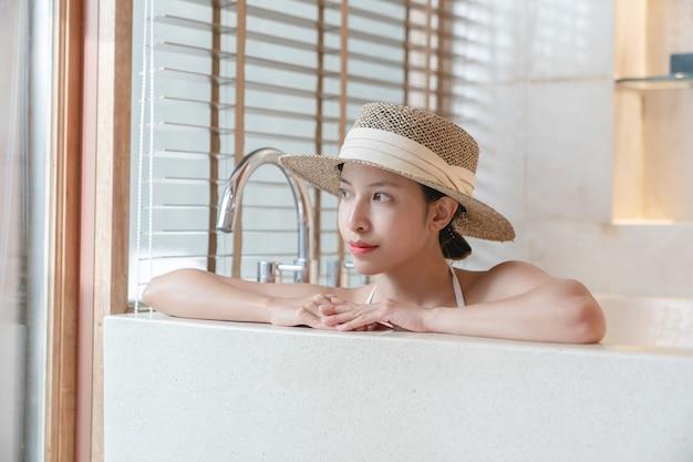 Kobieta ubrana w bikini i słomkowy kapelusz relaks w wannie z hydromasażem. kuracja spa