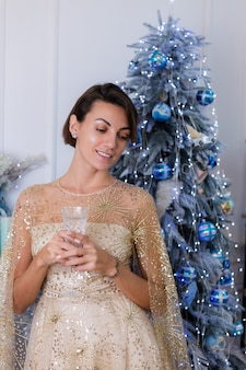Kobieta ubrana w błyszczącą złotą suknię wieczorową boże narodzenie trzyma kieliszek szampana przez niebiesko-zielone drzewo roku w domu