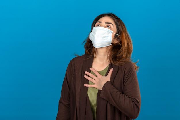 Kobieta ubrana w brązowy kardigan w medycznej masce ochronnej dotykająca klatki piersiowej w celu sprawdzenia płuc podczas oddychania przez odizolowaną niebieską ścianę