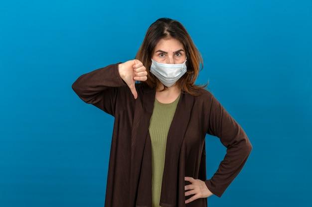 Kobieta ubrana w brązowy kardigan w medycznej masce ochronnej niezadowolona, pokazując kciuk w dół stojącego nad odizolowaną niebieską ścianą