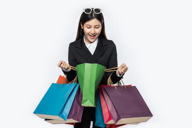 Kobieta ubrana w ciemne ubranie wraz z wieloma torbami na zakupy