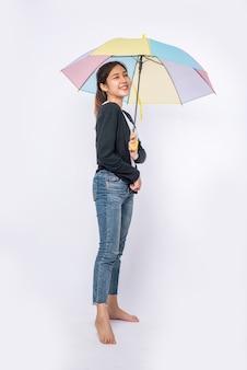 Kobieta ubrana w czarną koszulę i stojąca z parasolem