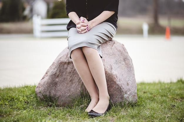 Kobieta ubrana w czarną koszulę i szarą spódnicę siedzi na skale w ogrodzie i modli się