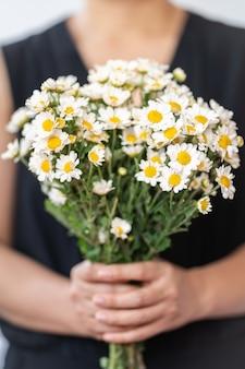 Kobieta ubrana w czarną sukienkę trzymając bukiet białych kwiatów daisy.