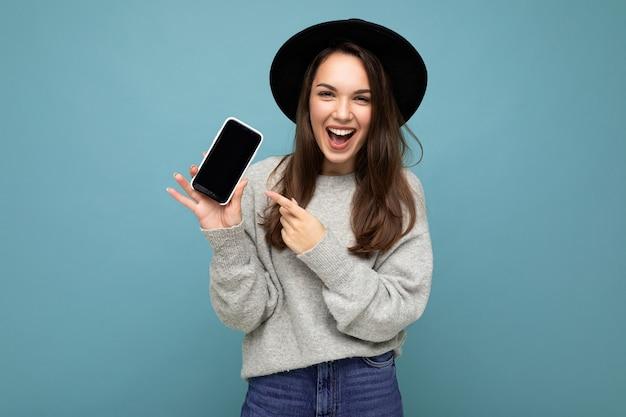 Kobieta ubrana w czarny kapelusz i szary sweter trzymając telefon patrząc na telefon wskazujący palec na ekranie na białym tle