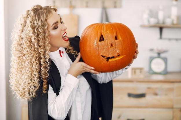 Kobieta ubrana w czarny kostium. pani z halloweenowym makijażem.