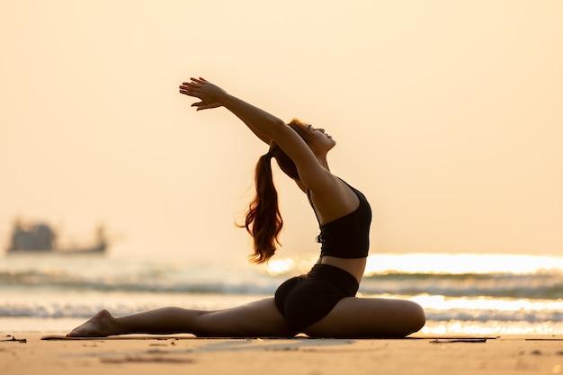 Kobieta ubrana w czarny sportowej ćwiczyć jogę pozowanie gołębi na plaży