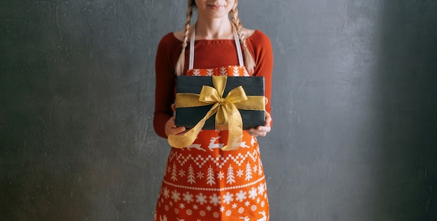 Kobieta ubrana w czerwoną sukienkę i świąteczny fartuch trzyma przed sobą pudełko.