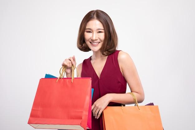 Kobieta ubrana w czerwoną sukienkę uśmiecha się trzymając torby na zakupy
