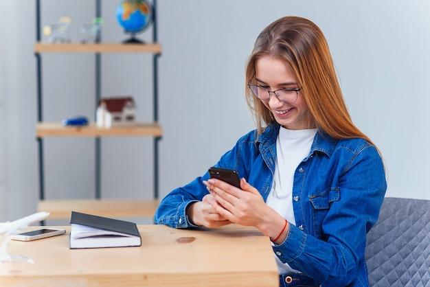 Kobieta ubrana w dżinsową koszulę siedzi przy stole podczas planowania podróży wakacje korzysta z inteligentnego telefonu.