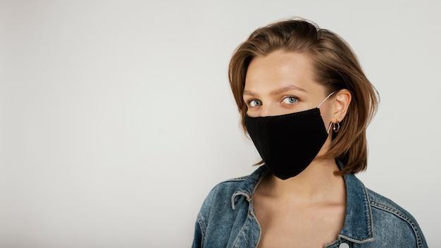 Kobieta ubrana w dżinsową kurtkę i maskę