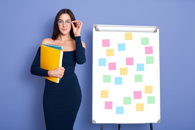 Kobieta ubrana w elegancką sukienkę i okulary, trzymając w rękach papierowe foldery, stojąc usłyszeć tablicę z naklejkami na niebieskim tle