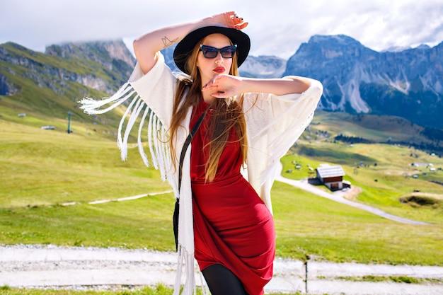 Kobieta ubrana w elegancki luksusowy strój w stylu boho, pozuje w niesamowitych dolomitach