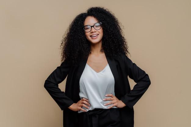 Kobieta ubrana w eleganckie czarne ubrania, trzyma obie ręce na biodrach