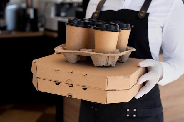 Kobieta ubrana w fartuch i trzymająca zapakowane jedzenie na wynos i filiżanki kawy