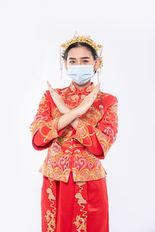 Kobieta ubrana w garnitur i maskę cheongsam pokazuje, że ludzie nie noszą maski nie mogą przyjść na zakupy w chiński nowy rok