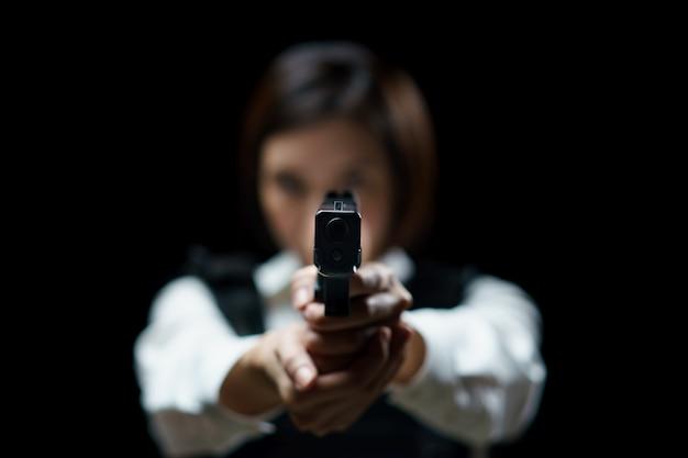 Kobieta ubrana w kamizelkę kuloodporną strzela z pistoletu w cel w zasięgu broni wewnętrznej.