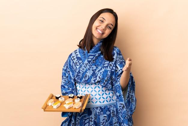 Kobieta ubrana w kimono i trzymając sushi na białym tle ściskając ręce za zamknięcie dobrej oferty